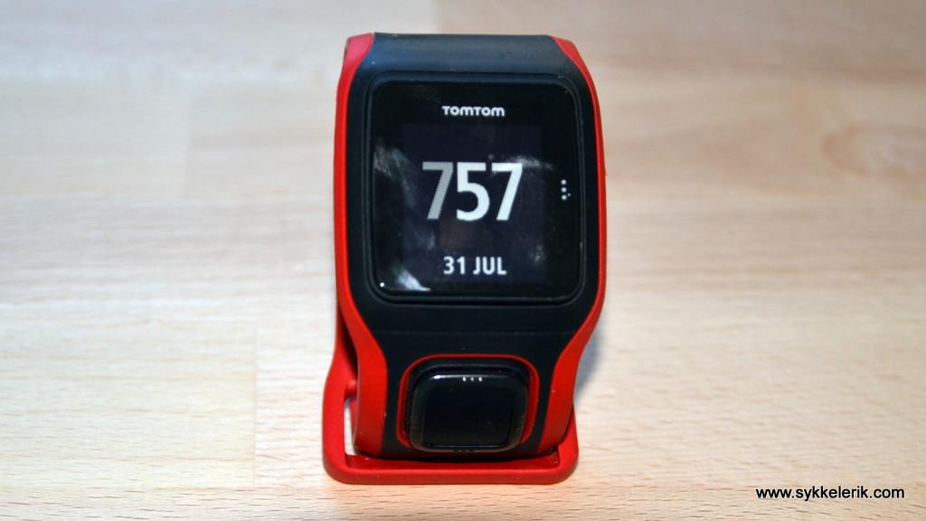 Tomtom Multisport Cardio sett forfra. Tydelig og lettlest display. Den firkantede knappen under skjermen brukes for å navigere i menyene.